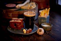 Η ατμόσφαιρα του παλαιού καφέ Ο φορέας με το δίσκο, ένα ποτήρι της σκοτεινής μπύρας, ψωμί σκόρδου και τηγανητά Γρήγορο φαγητό Στοκ Εικόνα