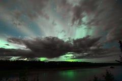 Η αυγή Borealis προκύπτει μέσω των σύννεφων μακρινή Αλάσκα στοκ εικόνες