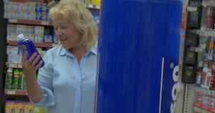 Η αυξημένη γυναίκα στο κατάστημα της πόλης Perea, Ελλάδα επιλέγει τα αγαθά απόθεμα βίντεο