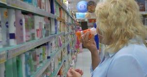 Η αυξημένη γυναίκα στο κατάστημα της πόλης Perea, Ελλάδα επιλέγει τα αγαθά από το ράφι απόθεμα βίντεο