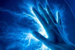 Η αφή του χεριού στη φωτεινή ηλεκτρική επιφάνεια-εκπομπή Στοκ Φωτογραφία