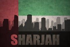 Η αφηρημένη σκιαγραφία της πόλης με το κείμενο Σάρτζα στα εκλεκτής ποιότητας Ηνωμένα Αραβικά Εμιράτα σημαιοστολίζει στοκ εικόνες