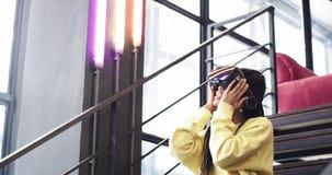 Η αφρικανική νέα γυναίκα πολύ εντυπωσίασε το παιχνίδι με τα γυαλιά μιας εικονικής πραγματικότητας σε ένα σύγχρονο γραφείο, αυτή σ φιλμ μικρού μήκους