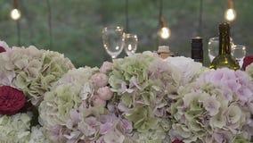 Η αψίδα για τα newlyweds είναι διακοσμημένη με τα λουλούδια και τα γυαλιά φιλμ μικρού μήκους