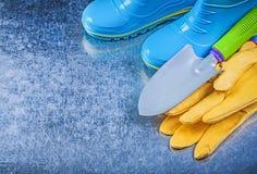 Η αδιάβροχη λαστιχένια ασφάλεια μποτών φορά γάντια στο φτυάρι χεριών στη μεταλλική ΤΣΕ Στοκ εικόνα με δικαίωμα ελεύθερης χρήσης