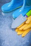 Η αδιάβροχη ασφάλεια μποτών γόμμας φορά γάντια στο φτυάρι χεριών στο μεταλλικό backgr Στοκ Φωτογραφίες