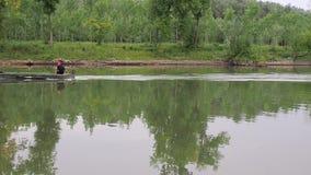 Η βάρκα μηχανών επιπλέει από τον ποταμό, κυματίζοντας νερό, ίχνος βαρκών μηχανών, καλοκαίρι, πράσινα δέντρα απόθεμα βίντεο