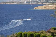 Η βάρκα μηχανών οδηγά τους τουρίστες σε ένα διογκώσιμο στρώμα στη Ερυθρά Θάλασσα κοντά στην παραλία στη παραθεριστική πόλη Sheikh Στοκ Εικόνες
