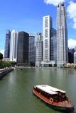 Η βάρκα πλοηγεί τον ποταμό Σινγκαπούρης Στοκ Φωτογραφίες