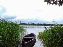 Η βάρκα στη λίμνη μεταξύ της πράσινης χλόης στοκ εικόνες