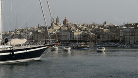 Η βάρκα Luzzu κρουαζιέρας swimms κοντά και μαρίνα γιοτ φιλμ μικρού μήκους