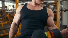 Η βάρος-ανύψωση στη γυμναστική - νέο μυϊκό άτομο εκτελεί την κατάρτιση για τους δικέφαλους μυς με τους αλτήρες - κλείνει επάνω φιλμ μικρού μήκους