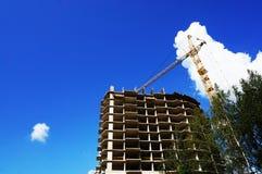 Η βάση ενός σπιτιού κάτω από την κατασκευή, ένας λειτουργώντας γερανός πύργων ενάντια στο μπλε ουρανό στο θερινό καιρό στοκ εικόνες