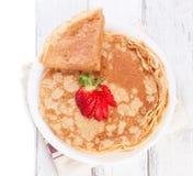 Η βάση των χρυσών τηγανιτών ζύμης σίτου ή crepes, παραδοσιακός για τη ρωσική εβδομάδα τηγανιτών, με τη φρέσκια φράουλα σε έναν ξύ Στοκ εικόνα με δικαίωμα ελεύθερης χρήσης