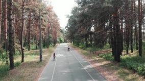 Η βέβαια ελκυστική γυναίκα αρχίζει το οδικό ποδήλατό της στην πορεία ποδηλάτων στο πάρκο r Άποψη κηφήνων απόθεμα βίντεο