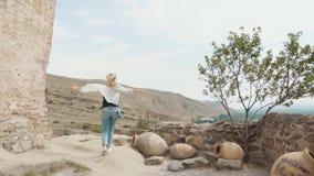Η βέβαια νέα γυναίκα με την ελαφριά πετώντας τρίχα στην παλαιά αρχαία της Γεωργίας πόλη, κυρία στην άσπρα μπλούζα και τα τζιν περ φιλμ μικρού μήκους