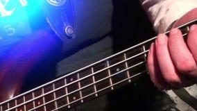 Η βαθιά κιθάρα στη ζωντανή δράση σε μια συναυλία - εστίαση ραφιών - κλείνει επάνω απόθεμα βίντεο