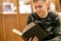 Η βιβλιοθήκη συνεδρίασης νεαρών άνδρων στο σπίτι και διαβασμένος ένα βιβλίο, ψύχρα και χαλαρώνει το φ στοκ εικόνες