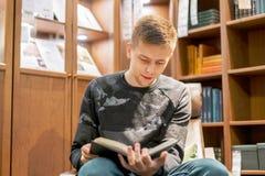 Η βιβλιοθήκη συνεδρίασης νεαρών άνδρων στο σπίτι και διαβασμένος ένα βιβλίο, ψύχρα και χαλαρώνει το φ στοκ εικόνα