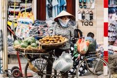 Η βιετναμέζικη γυναίκα που φορά το ασιατικό κωνικό καπέλο πωλεί τα φρούτα στο ποδήλατό της στην οδό του Ανόι, Βιετνάμ Στοκ φωτογραφία με δικαίωμα ελεύθερης χρήσης