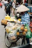 Η βιετναμέζικη γυναίκα που φορά το ασιατικό κωνικό καπέλο πωλεί τα φρούτα στο ποδήλατό της στην οδό του Ανόι, Βιετνάμ Στοκ Εικόνα