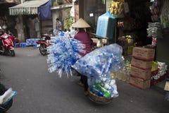 Η βιετναμέζικη γυναίκα φέρνει τα παλαιά πλαστικά μπουκάλια Στοκ Εικόνες
