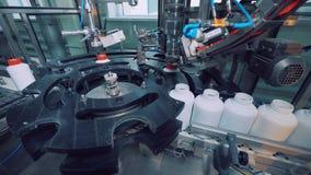 Η βιομηχανική μηχανή βιδώνει τα καλύμματα στα πλαστικά βάζα απόθεμα βίντεο