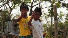 Η βιρμανίδα τοποθέτηση παιδιών και παρουσιάζει στα σημάδια νίκης ομαλό ζουμ φιλμ μικρού μήκους