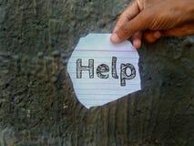 Η βοήθεια λέξης που γράφεται στην εκμετάλλευση κομματιών χαρτί υπό εξέταση στοκ εικόνα με δικαίωμα ελεύθερης χρήσης