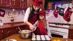 Η βοήθεια μητέρων η κόρη της βάζει μια ακατέργαστη ζύμη στη μορφή της Λευκής Βίβλου για το cupcake απόθεμα βίντεο