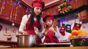 Η βοήθεια μητέρων η κόρη της βάζει μια ακατέργαστη ζύμη στη μορφή της Λευκής Βίβλου για το cupcake φιλμ μικρού μήκους