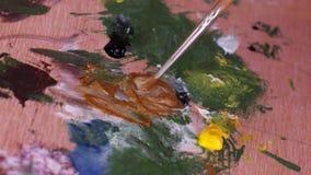 Η βούρτσα που βυθίζει στο χρώμα στην παλέτα απόθεμα βίντεο