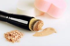 Η βούρτσα σύνθεσης, τα σφουγγάρια, η βάση κηλίδων makeup και το πρόσωπο κονιοποιούν σε ένα W Στοκ Φωτογραφίες