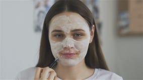 Η βούρτσα χρήσης γυναικών στην εφαρμογή της καλλυντικής μάσκας στο δωμάτιο και εξετάζει τη κάμερα φιλμ μικρού μήκους