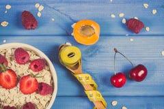 Η βρώμη ξεφλουδίζει με τα φρούτα και το μέτρο ταινιών με το κουτάλι, την έννοια του αδυνατίσματος και την υγιή διατροφή Στοκ Εικόνες