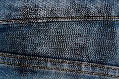 Η βρώμικη κινηματογράφηση σε πρώτο πλάνο Grunge του ξεπερασμένου τζιν παντελόνι δένει τη σύσταση τζιν, το μακρο υπόβαθρο για τον  Στοκ εικόνα με δικαίωμα ελεύθερης χρήσης