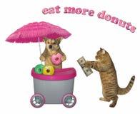 Η γάτα αγοράζει donuts από ένα σκυλί στοκ φωτογραφίες