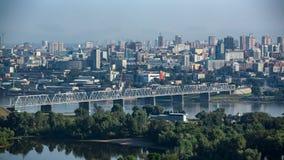 Η γέφυρα σιδηροδρόμων πέρα από τον ποταμό ενάντια στο σκηνικό μιας σύγχρονης πόλης στοκ φωτογραφία με δικαίωμα ελεύθερης χρήσης