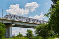 Η γέφυρα σιδηροδρόμων πέρα από τον ποταμό φορά, στο υπόβαθρο του νεφελώδους s Στοκ εικόνα με δικαίωμα ελεύθερης χρήσης