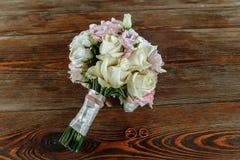 Η γαμήλια ανθοδέσμη της κρέμας και των ρόδινων τριαντάφυλλων βρίσκεται σε μια ξύλινη επιφάνεια γαμήλιο λευκό δαχτυλιδιών ανασκόπη Στοκ Εικόνα