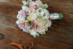 Η γαμήλια ανθοδέσμη της κρέμας και των ρόδινων τριαντάφυλλων βρίσκεται σε μια ξύλινη επιφάνεια γαμήλιο λευκό δαχτυλιδιών ανασκόπη Στοκ Φωτογραφίες