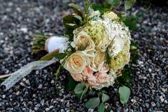 Η γαμήλια ανθοδέσμη της κρέμας και των ρόδινων τριαντάφυλλων βρίσκεται στις μικρές πέτρες Στοκ φωτογραφίες με δικαίωμα ελεύθερης χρήσης