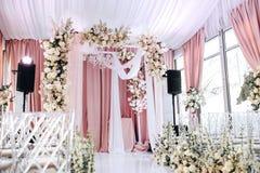 Η γαμήλια ζώνη είναι διακοσμημένη με το λευκό και το ύφασμα ροδάκινων, τον πολυέλαιο κρυστάλλου, τις διαφανείς καρέκλες για τους  στοκ εικόνες