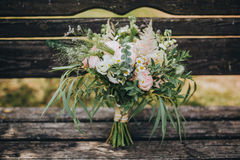Η γαμήλια ανθοδέσμη των λουλουδιών και της πρασινάδας είναι σε έναν παλαιό ξύλινο πάγκο Στοκ Φωτογραφίες