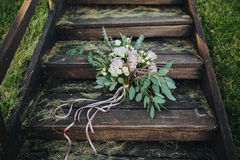 Η γαμήλια ανθοδέσμη των λουλουδιών και της πρασινάδας είναι στα παλαιά ξύλινα σκαλοπάτια στο δάσος στοκ εικόνες