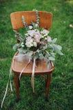 Η γαμήλια ανθοδέσμη των λουλουδιών και της πρασινάδας στέκεται σε μια ξύλινη καρέκλα στην πράσινη χλόη στο δάσος Στοκ φωτογραφία με δικαίωμα ελεύθερης χρήσης