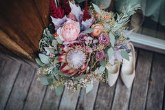 Η γαμήλια ανθοδέσμη των λουλουδιών και των πρασίνων με την κορδέλλα στέκεται σε ένα ξύλινο πάτωμα δίπλα στα παπούτσια νυφών ` s Στοκ Εικόνες