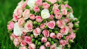Η γαμήλια ανθοδέσμη των ρόδινων τριαντάφυλλων βρίσκεται στην πράσινη χλόη απόθεμα βίντεο