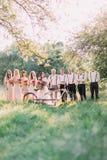 Η γαμήλια σύνθεση εάν τα newlyweds, οι παράνυμφοι και τα καλύτερα άτομα πίσω από το άσπρο ποδήλατο στη μέση του ηλιόλουστου Στοκ Εικόνες