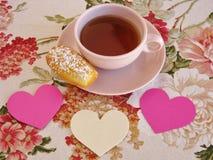 Η γαλλικά Madeleine και τσάι στο ρόδινο εκλεκτής ποιότητας φλυτζάνι στο floral τραπεζομάντιλο με τις καρδιές Στοκ Εικόνα